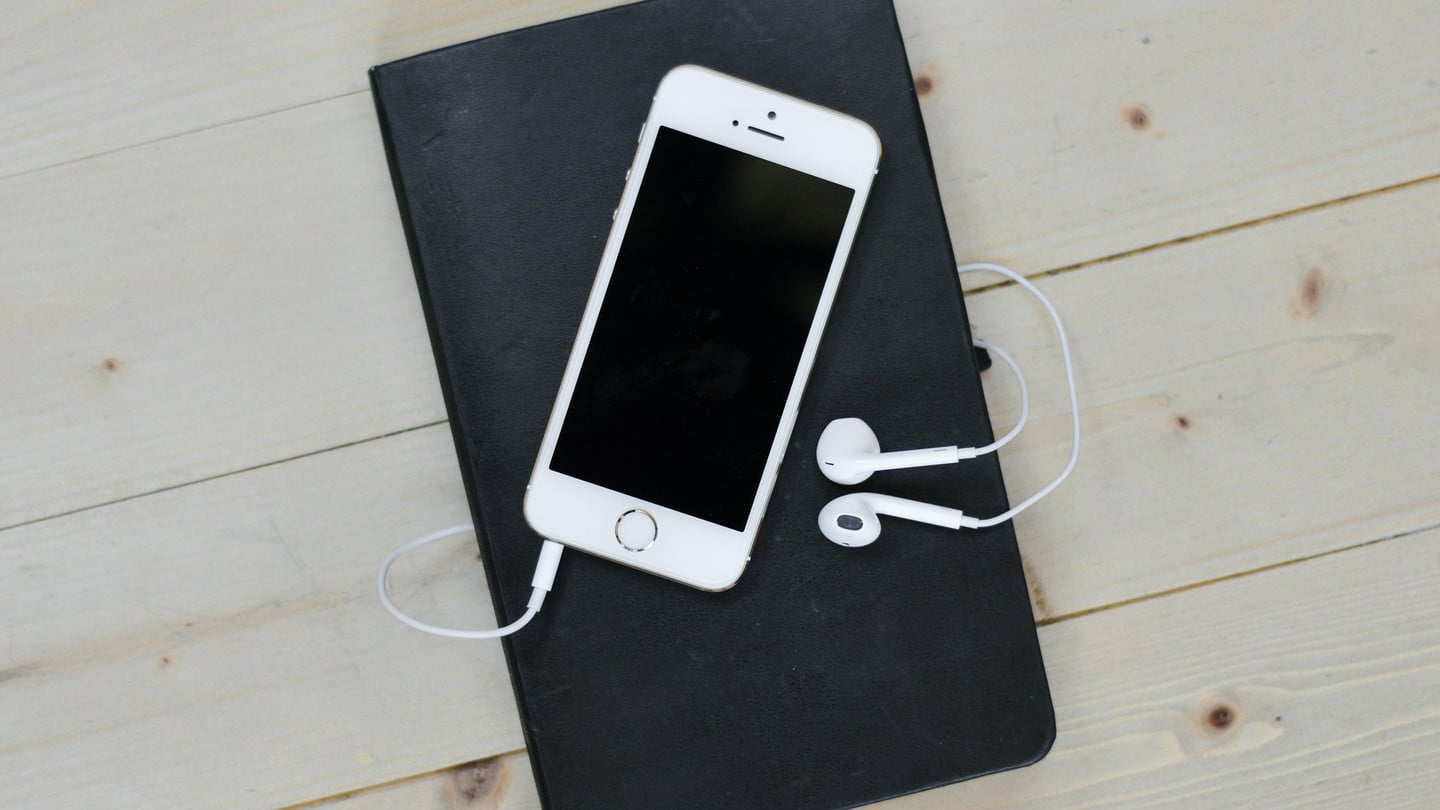 iPhone with earphones and notebook